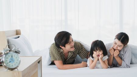 Photos of warm and lovely Asian families. Parents are playing happily and happily with their little daughter in the bedroom. Being happy to be with family on holidays