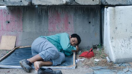 Asian homeless man lying beside the wall His face is full of suffering, depression, and despair. People are unemployed due to the effects of the corona virus outbreak.
