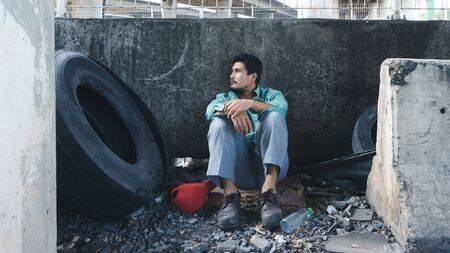 An Asian homeless man is sitting by the wall. His face is full of suffering, depression and despair. People are unemployed due to the effects of the corona virus outbreak. Stock Photo