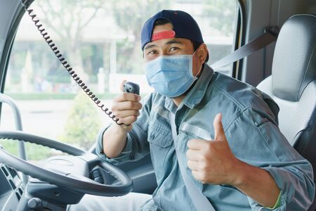 Close-up photos of Asian truck drivers wearing masks to protect against dust and the spread of the flu. Covid 19. Inside the car front