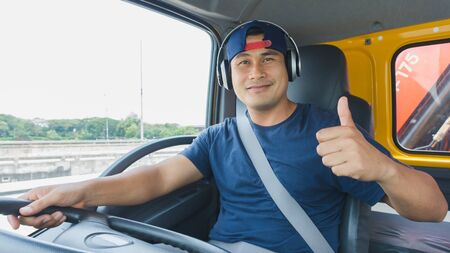 An Asian male truck driver is driving down the road with caution. He uses headphones to talk on the phone and listen to music.
