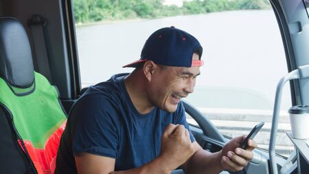 Asian truck drivers are using their smartphones to communicate happily in the car. Fast, fast wireless communication with high-speed internet. Stock Photo