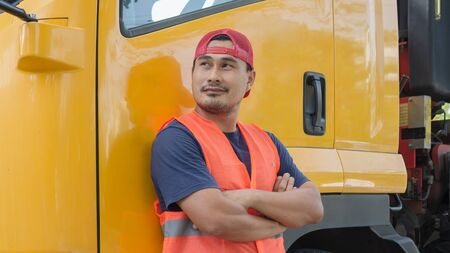 An Asian man was smiling happily beside the yellow truck. He has a career as a transport driver. The transportation business never stops. It must be driven and traveled all the time.