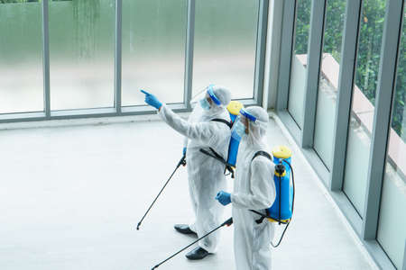 Professional male worker In protective clothing and masks are spraying disinfectants, cleaning, controlling virus and bacteria in the contaminated area After the spread of coronavirus or COVID-19 Reklamní fotografie