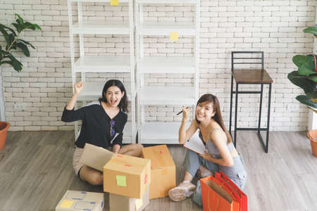 Merchant Two attractive young Asian women make living selling products online. They are checking the boxes to send customers. They use communication technology and the internet to market 写真素材