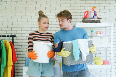 A young couple of Caucasian people do chore together. Attractive modern husbands and wives smile happily and prepare for laundry and house cleaning. Service provided by professional cleaners
