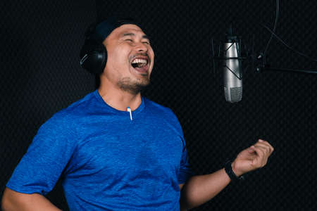 Confident Asian mature young man and a microphone Practice singing in the recording studio. Artist audition for media, music, and performance producer.