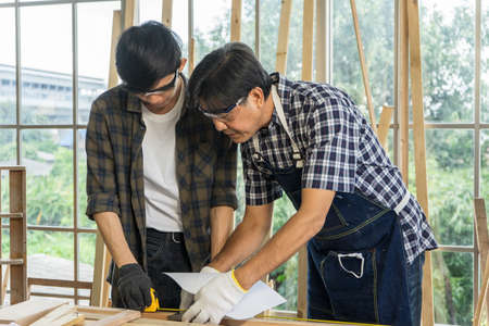 senior father and a growing son are working on wood and repairing the house together. carpenter is working on wood crafts in the furniture factory. Banco de Imagens