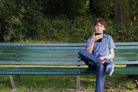 ereader: A man reading an e-reader on a bench