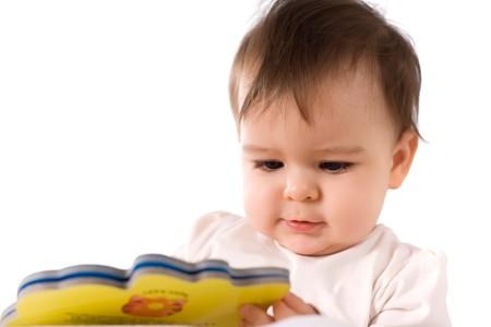 adorable baby girl reading a book photo