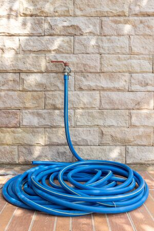 Water tap and garden hose with brick wall
