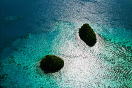 two small islands in palau with sunshine glittering sea