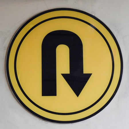 The transportation yellow sign of allowed u-turning point are sticked at the wall in parking building to signalize motor vehicle drivers to know the direction Banco de Imagens - 100620095