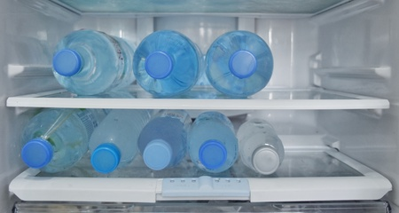 Clear bottles of clean fresh drinking water are refridgerated in a refridgerator to make and keep  its coldness for drinking when people are thirsty