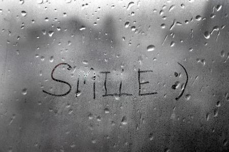 Handmade word smile on the wet glass window Stock Photo