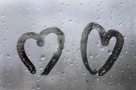 two hearts painted on glass in Rainy weather there are many drops on it Stock fotó