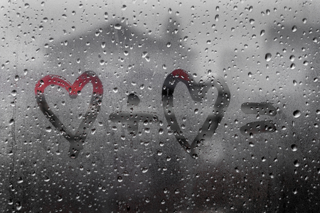 two hearts with plus sing and equality sign on window in Rainy weather , valentine's day Imagens