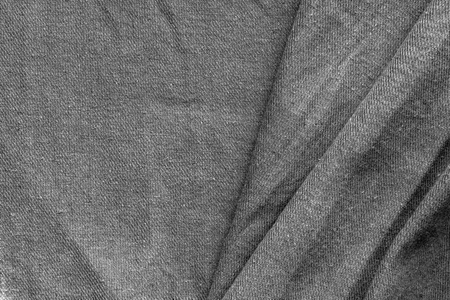 Relief of the folds of dark gray fabric with a Christmas tree pattern as a background