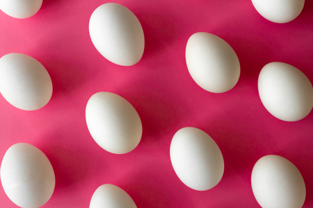 High angle view of isolated white eggs on bright pink color background. concept Easter Stok Fotoğraf