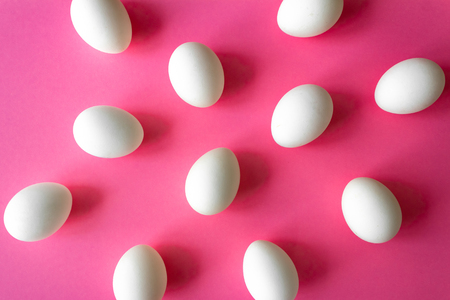 Pattern made of white eggs on bright pink color background. Easter concept