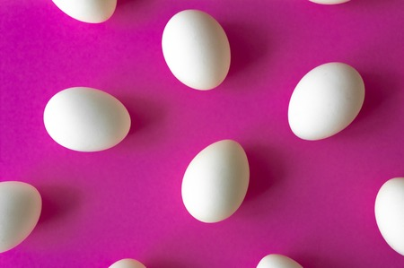 Pattern made of white eggs on purple background. Easter concept
