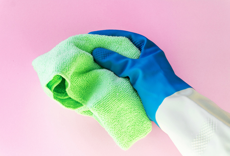 Hand in color rubber protective glove holds a bright microfiber duster isolated on the pink background. accssesouries for different surfaces in room, bathroom, kitchen. Early spring or regular cleanup