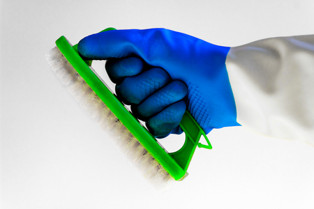 A hand in a protective rubber glove holds on a white background a bright synthetic brush. The concept of bright spring, spring cleaning, cleaning tools, cleaning of the bathroom and the kitchen.
