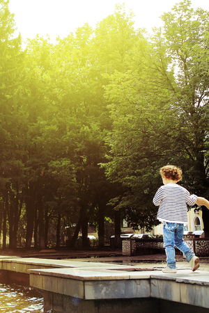 charming happy little child in the sunlight walks in the park in the summer, his hand is held so as not to fall