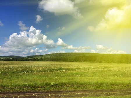 field of green grass, blue sky with clouds and sun rays