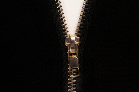 Open zipper or clothes lock on black fabric, close up photo