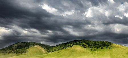 panoramic view of green hills are illuminated by the sun on dark blue sky with cumulus clouds background. before a thunderstorm and heavy rain