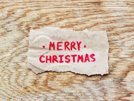piece of rough paper with an inscription in red pencil Merry Christmas lies on a smooth wooden board with an oak texture, a strong postcard, a top view, in the middle an inscription