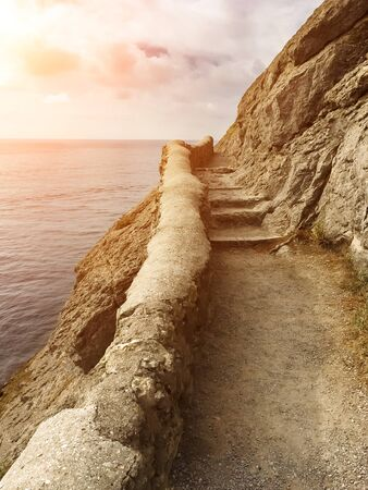 edge of the cliff with an ancient stone path along the sea with stone steps against the sea with the setting sun, vertical frame in the Crimea on the path of golitsina, stairway to heaven