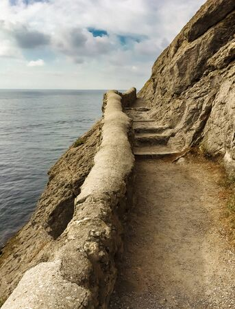 edge of the cliff with an ancient stone path along the sea with stone steps against the sea and clouds, vertical frame in the Crimea on the path of golitsina, stairway to heaven