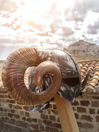 Viking helmet with round large horns on the background of an ancient tiled roof