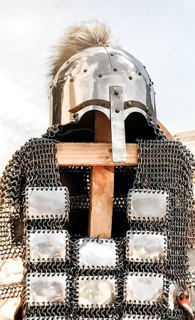 antique warrior armor, shiny metal helmet with nose protection and fur decoration, shirt with metal plates, armor thrown over wooden slats as exhibits at the festival