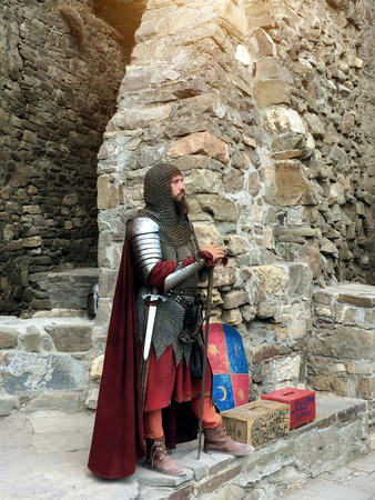 Sudak, Russia - August 16, 2015: powerful bearded man in a suit and image of a middle-aged knight in a helmet, chain, armor, with a sword in a belt standing at the ancient castle wall, rests on a sword during a historical reconstruction at the Festivals i