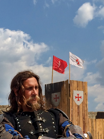 Sudak, Russia - August 16, 2015: brutal man with a beard, long hair and a stern look in the armor of a medieval knight against a wooden wall with flags and a coat of arms of the Crusaders