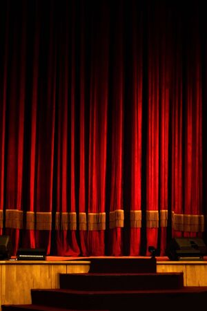 Theater stage with red curtain and steps lit by muted light