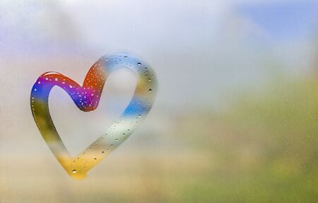 Color heart painted on sweaty glass, there are many drops on it, inscription heart and love using handmade on a wet autumn foggy glass. valentines day concept with copy space for text