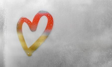 Red and orange heart painted on sweaty glass, there are many drops on it, inscription heart and love on a wet autumn foggy glass. valentines day concept with copy space for text