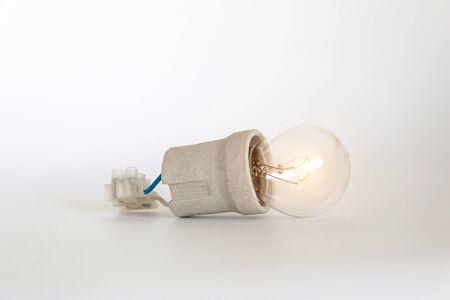L'ampoule d'éclairage à incandescence avec capuchon, douille, fils et bornier se trouve sur fond blanc. Ampoule Ilyich et Edison, nouveau concept d'idée