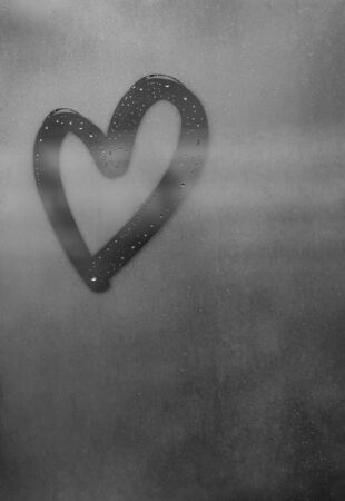 Dark gray heart painted on sweaty glass, there are many drops on it, inscription heart and love using handmade on a wet gray autumn foggy glass. valentines day concept with copy space for text Stock fotó