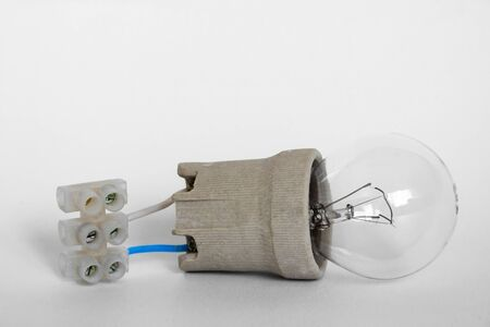 Lighting incandescent lamp bulb with cap, socket, wires and terminal block lies on white background. Bulb Ilyich and Edison, new idea concept