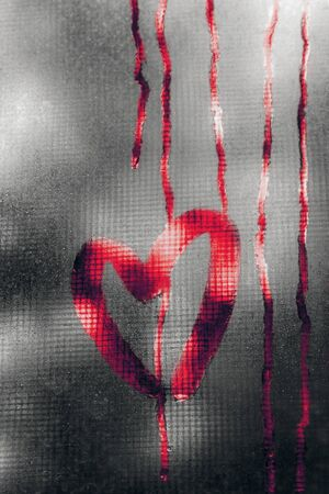 red bloody heart painted on sweaty glass in the fall in the rain, rain drops run down the glass and leave streaks. valentines day concept with copy space for text 写真素材