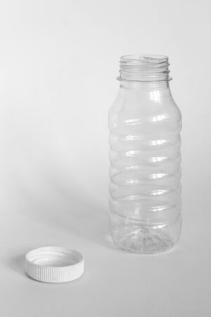 empty transparent open plastic bottle without cap, cap lies next to a white background, the concept of debris removal