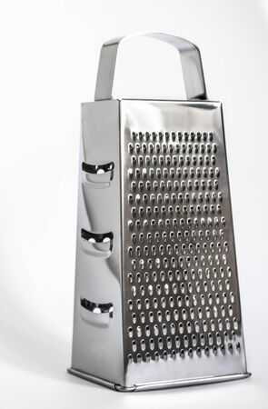 shiny metal new grater isolated on white background, close-up cheese and food stainless grater with slight shadow Stockfoto
