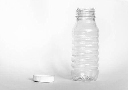 empty transparent open plastic bottle without cap, cap lies next to a white background, the concept of debris removal, copy space