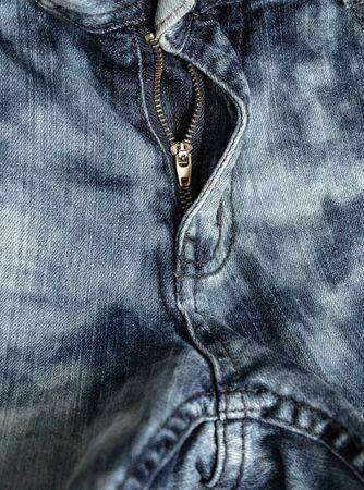 close-up zipper open on blue jeans, denim texture, zipper jeans pants half open, shabby denim fabric texture