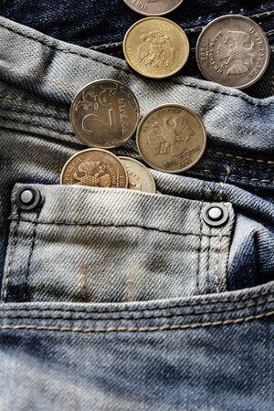 coins in blue jeans pocket close-up, finance and currency concept
